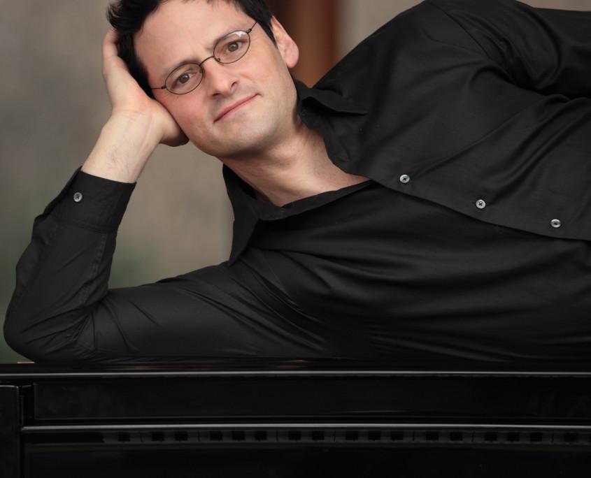 Pianist Tobias Forster, liegend auf Flügel, Porträt Pressefoto Hochformat, Foto anna.s.