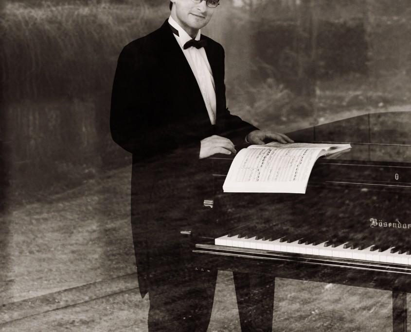 Pianist Tobias Forster, stehend am Flügel, Pressefoto, Foto anna.s.